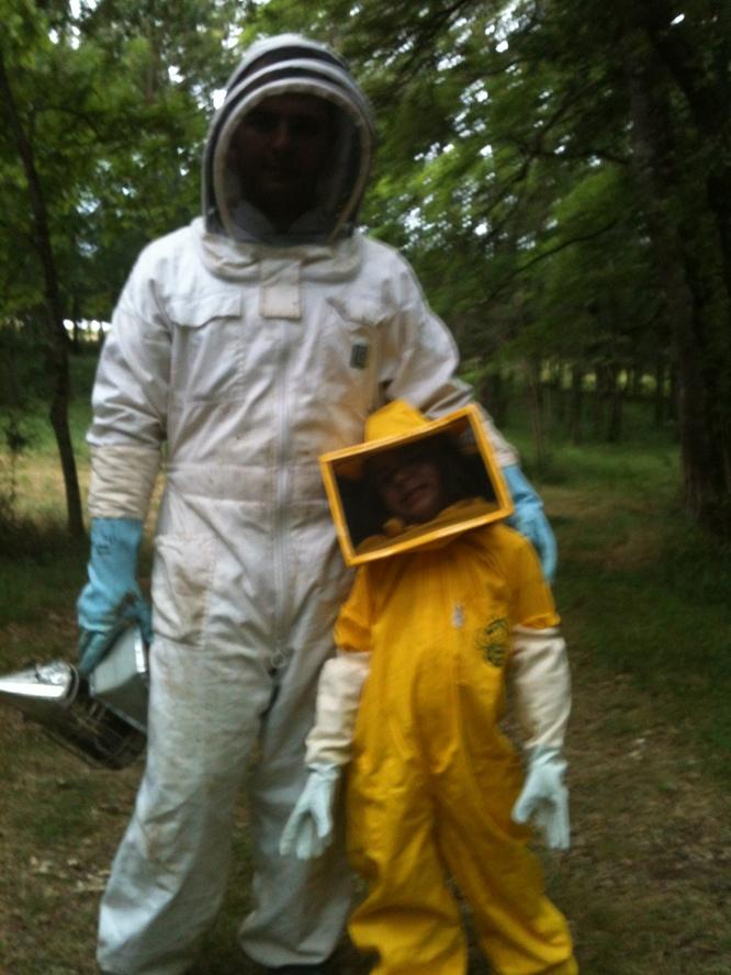 La petite accompagne papa aux abeilles